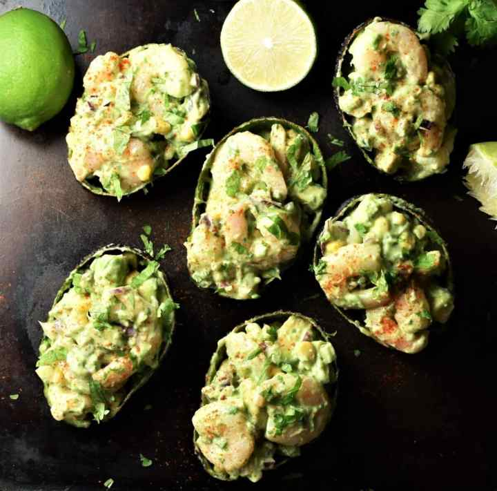 Top down view of stuffed avocado halves with limes in background.