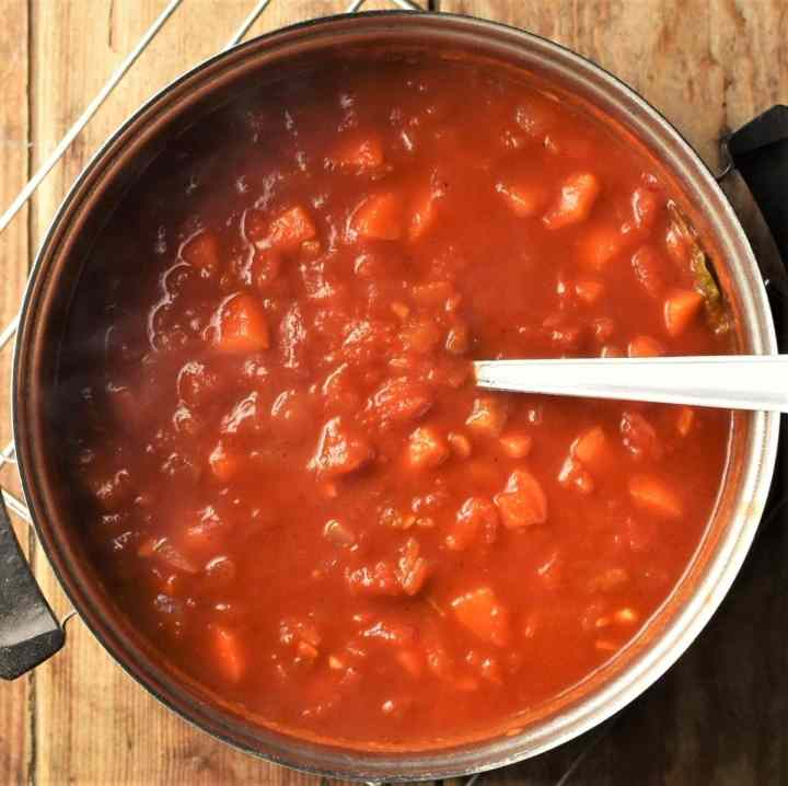 Tomato sauce with vegetables in pot with spoon.