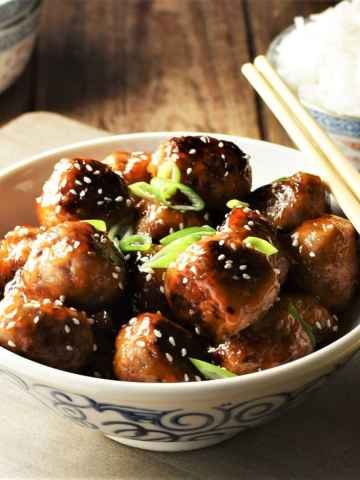 Close-up view of meatballs with glaze in bowl with chopsticks and rice in background.