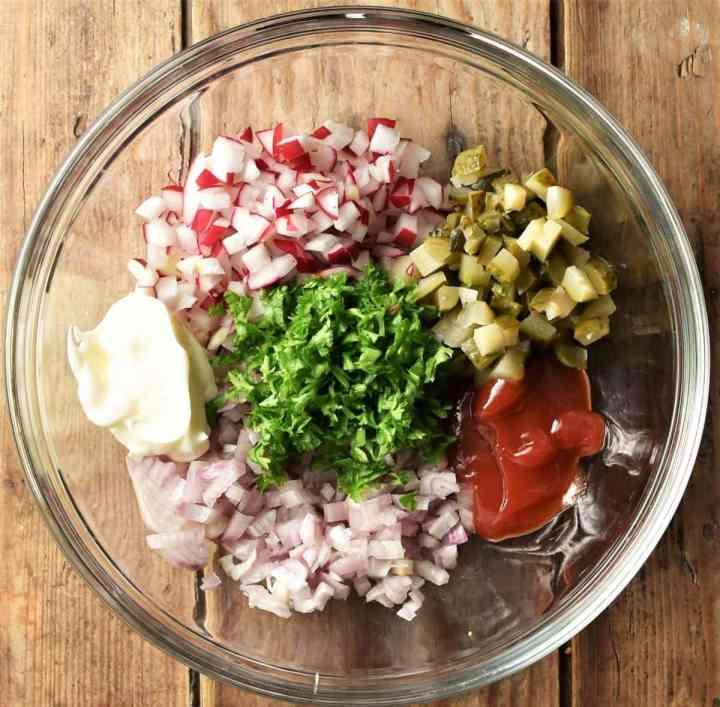 Chopped gherkins, shallots, radish, parsley and dollop of ketchup and mayonnaise in mixing bowl.