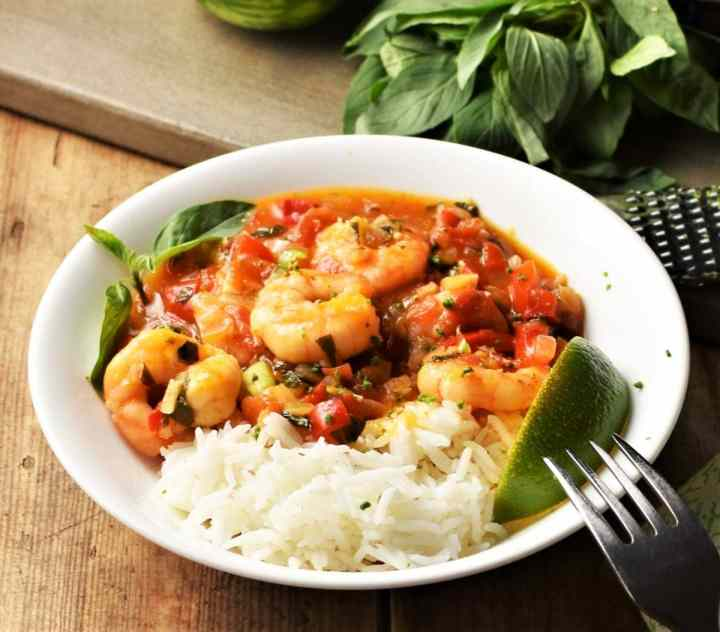 Side view of rice with shrimp in tomato sauce with lime wedges in white bowl.