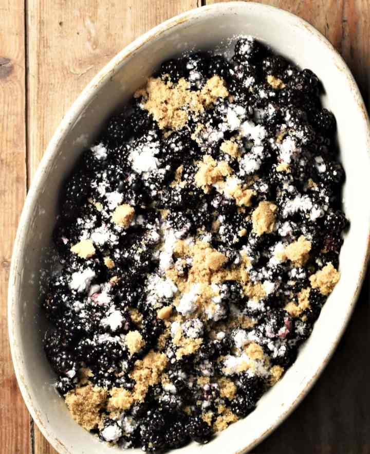 Blackberries with flour and brown sugar in white oval dish.