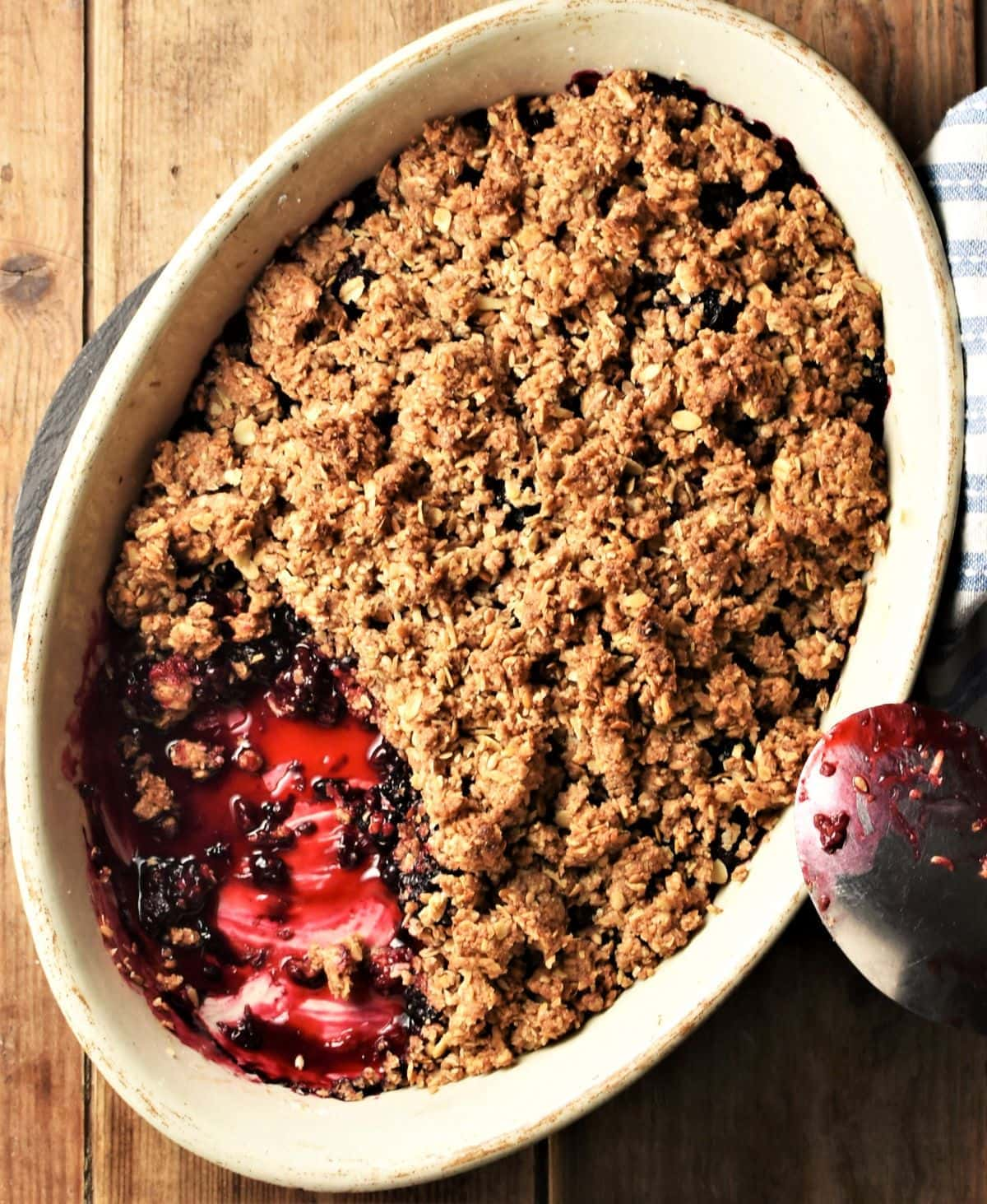 Top down view of blackberry crumble in white oval dish with spoon.