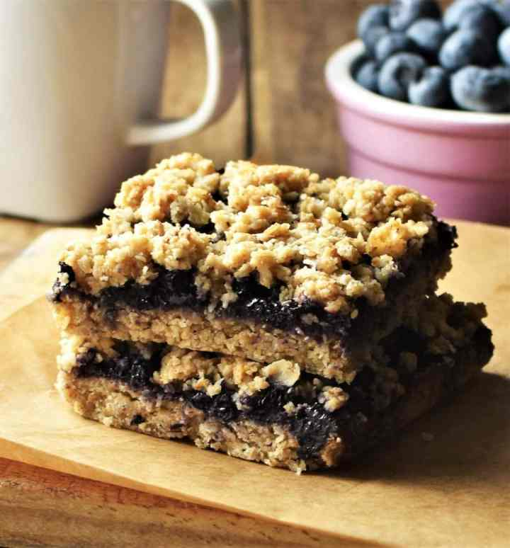 Side view of 2 blueberry bars, with white cup and blueberries in background.