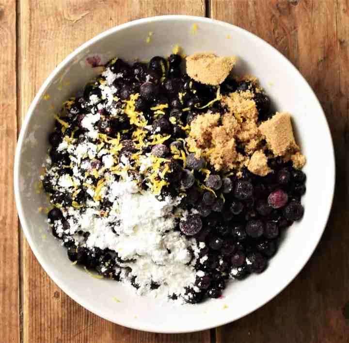 Blueberries, flour, sugar and lemon zest in white bowl.
