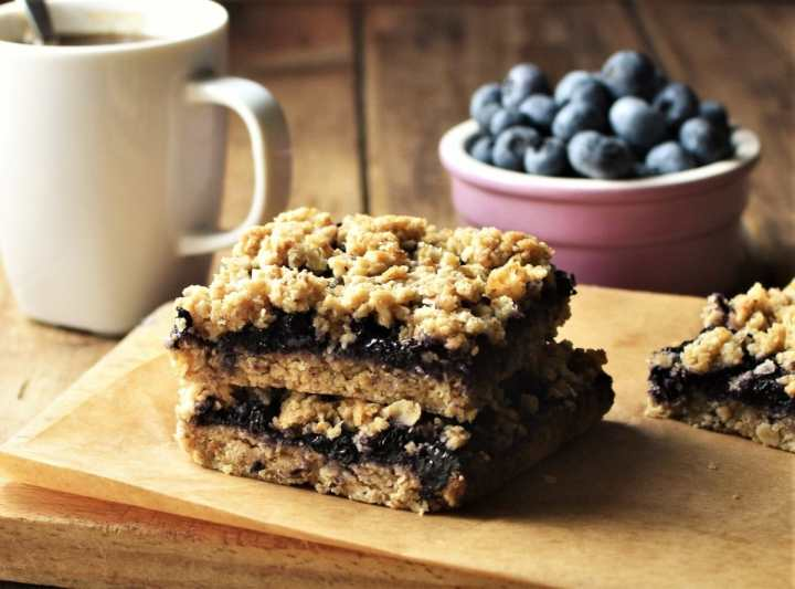 Side view of blueberry oatmeal bars on top of board, with white cup and blueberries in background.