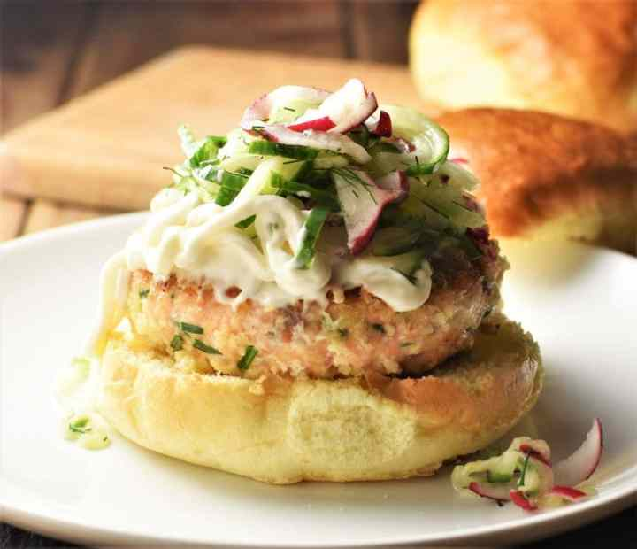 Salmon burger on top of bun with slaw and buns in background.