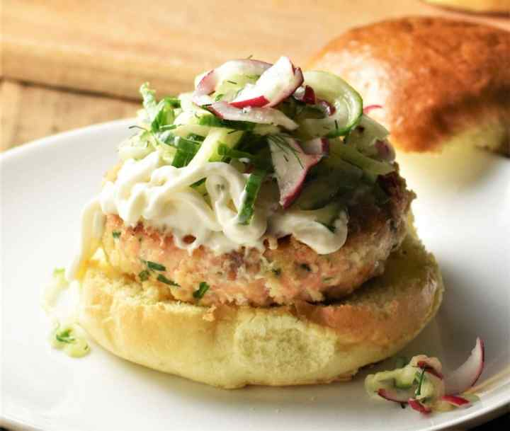 Side view of salmon burger topped with slaw and mayonnaise.