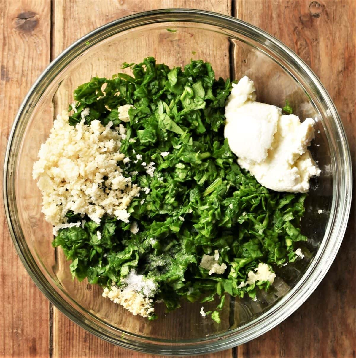 Spinach mixture with cheese and panko in mixing bowl.