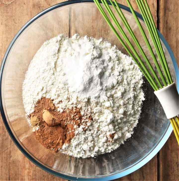 Carrot cake dry ingredients in mixing bowl with green whisk.