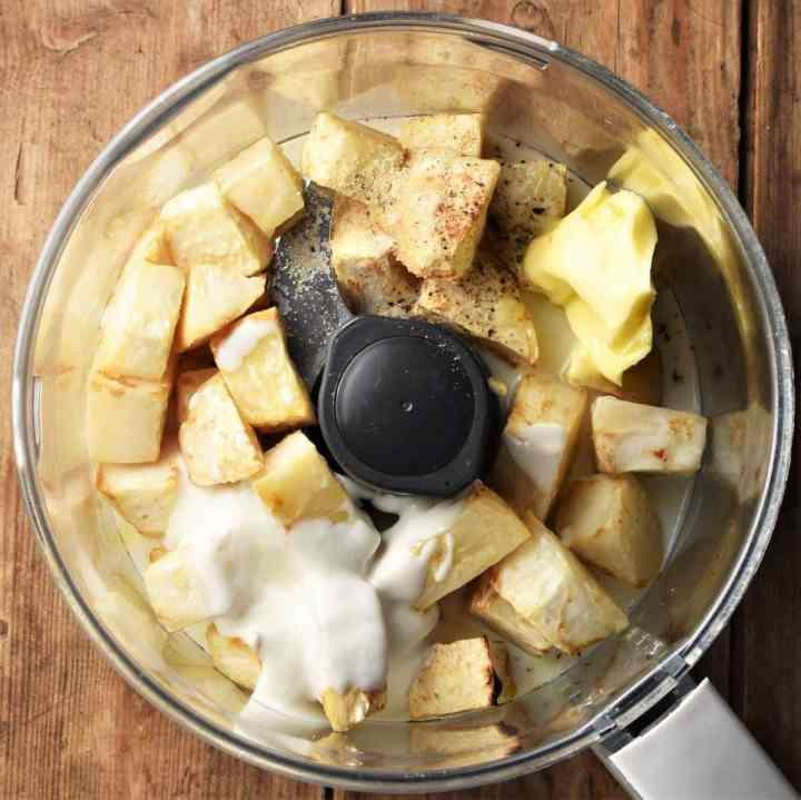 Cubed celeriac and yogurt in food processor bowl.