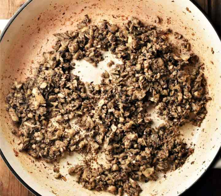 Finely chopped fried mushrooms in large pan.