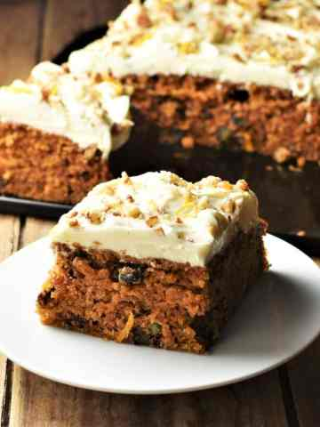 Side view of low fat carrot cake slice on white plate with cake in background.