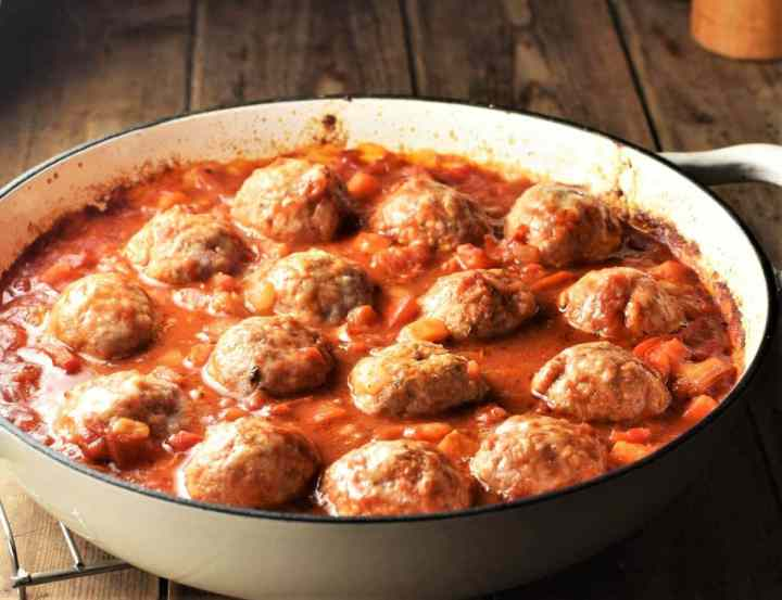 Side view of meatball casserole with vegetable sauce in white dish.
