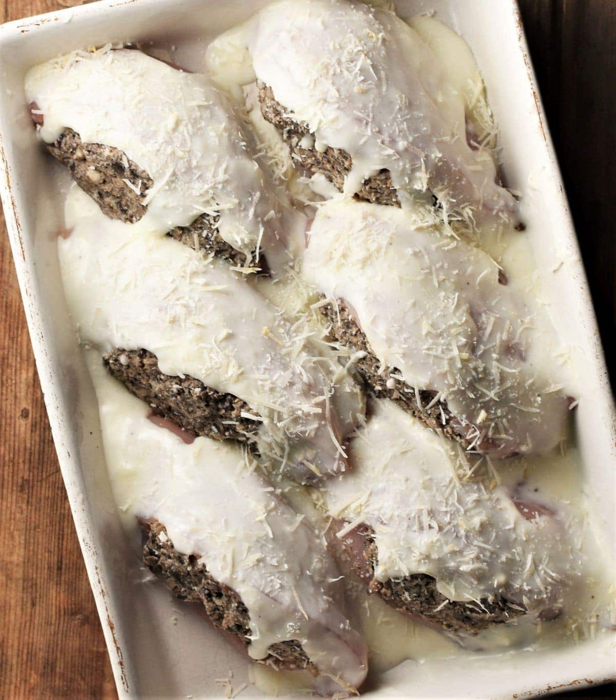 6 chicken breasts in creamy sauce in rectangular dish.