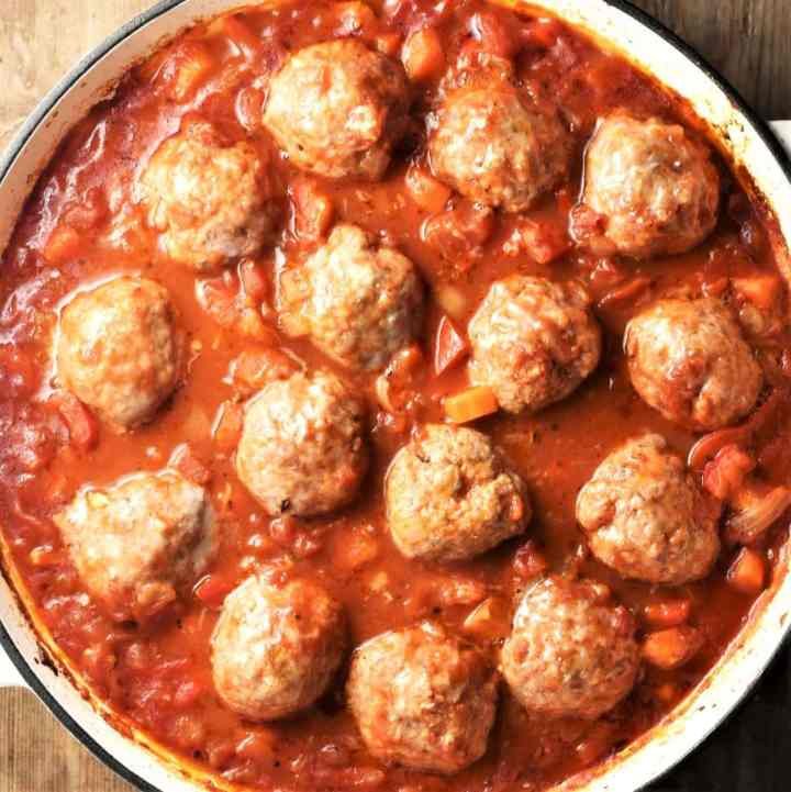 Top down view of meatballs in chunky vegetable sauce in white round dish.
