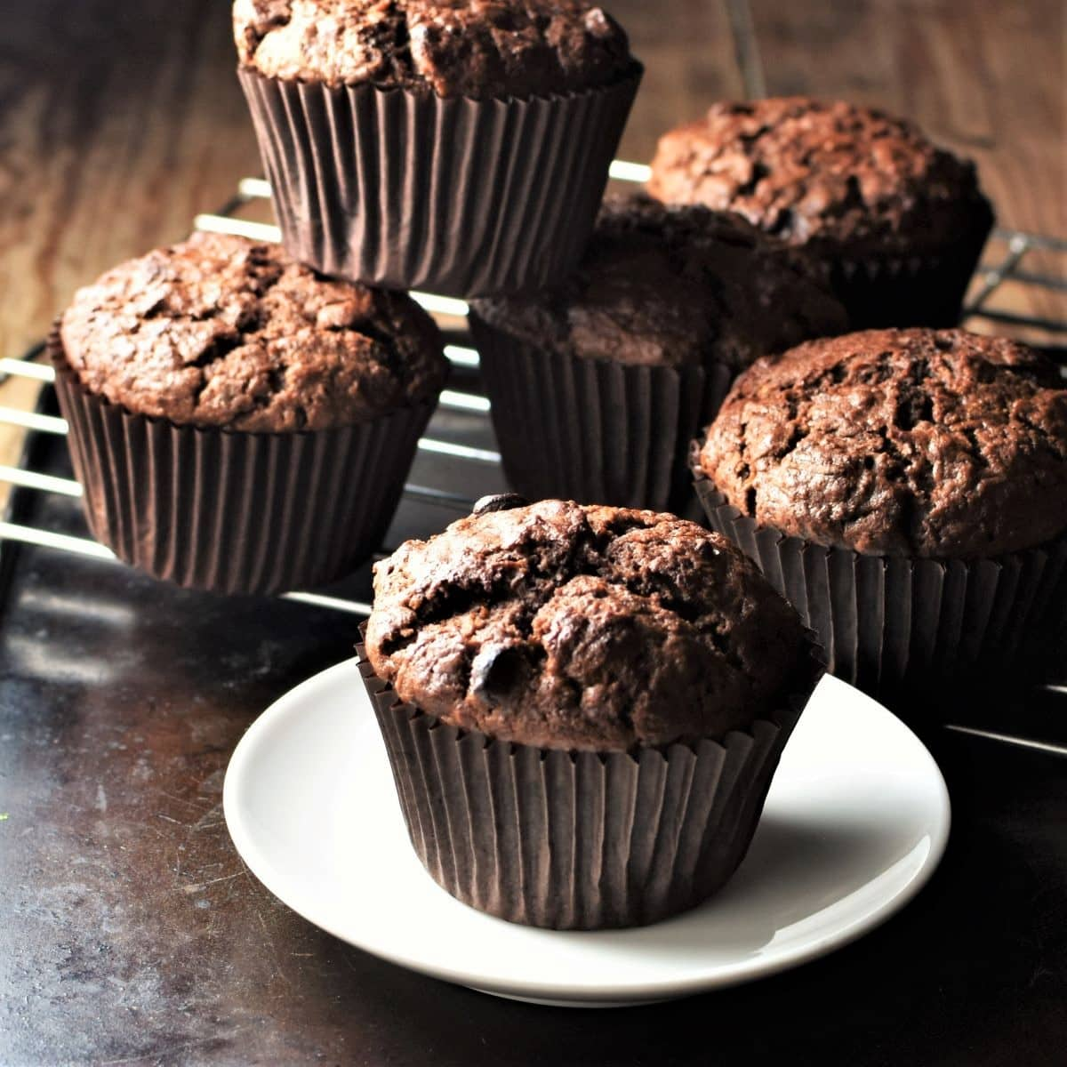 Side view of chocolate sweet potato muffins on plate and rack.