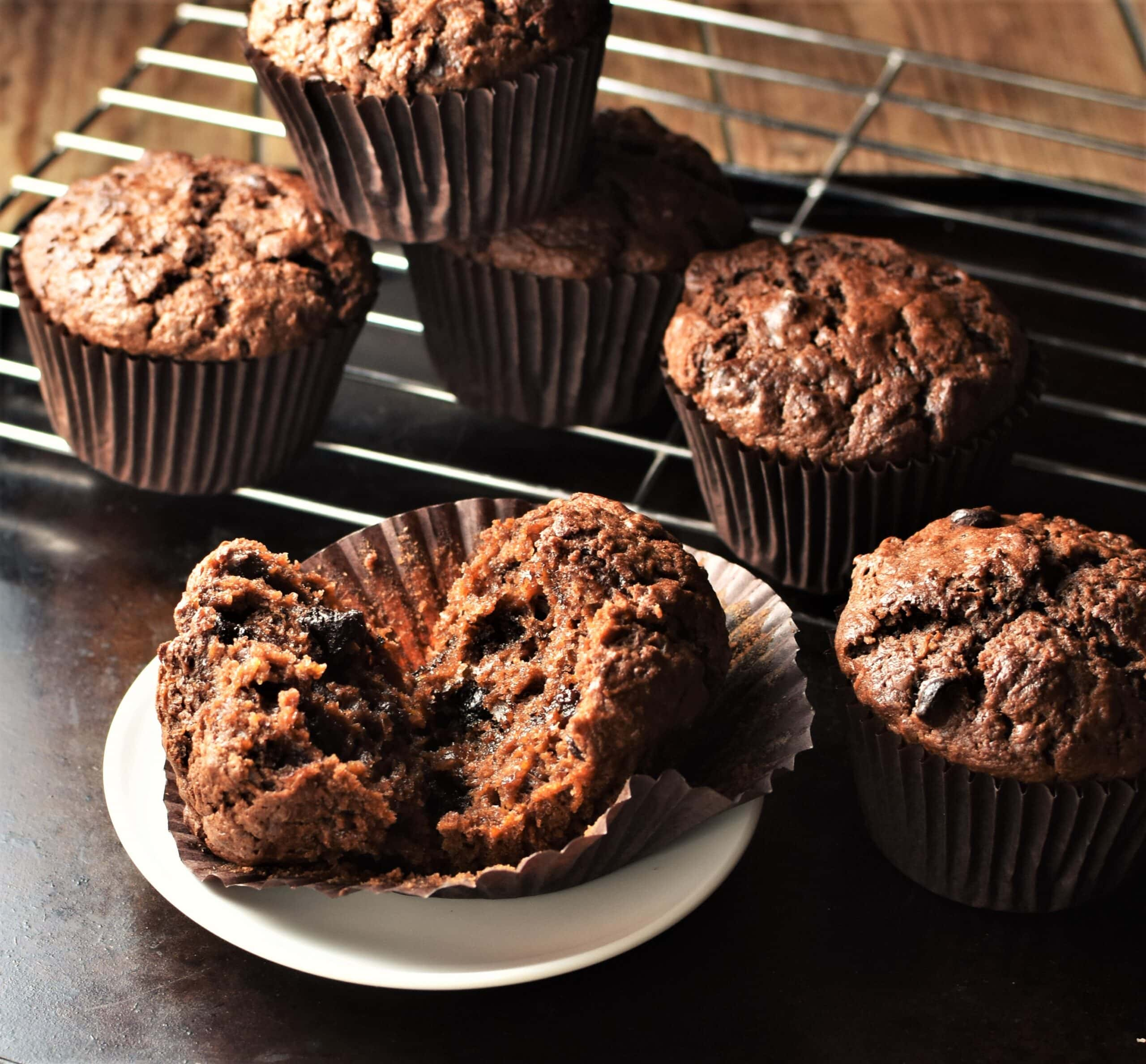 Side view of sweet potato chocolate muffins on white saucer and rack.