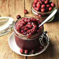 Side view of cranberry chutney in open jar with spoon and cranberries in background.