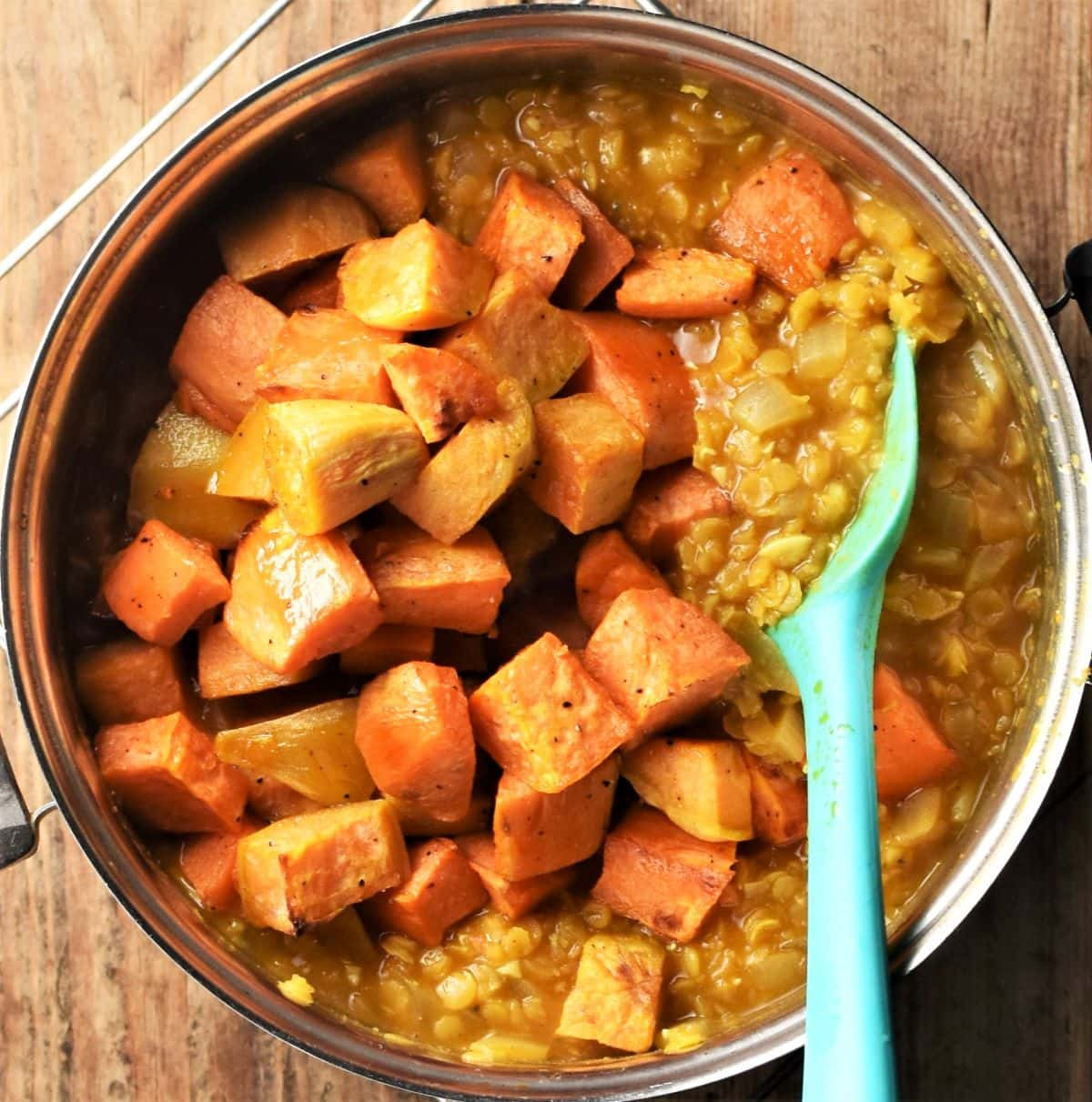 Cubed roasted sweet potato being stirred into dahl.