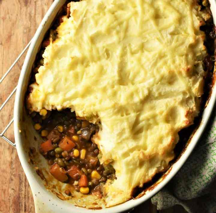 Top down partial view of lentil vegetable shepherd's pie in oval dish.