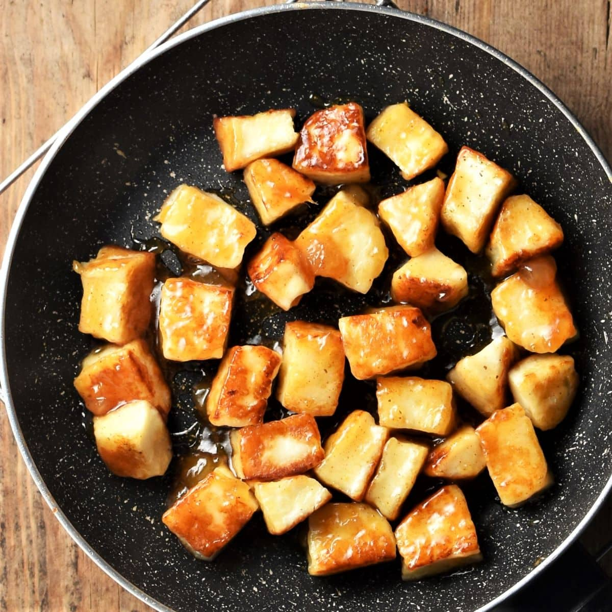 Cubed fried halloumi coated in chutney in pan.