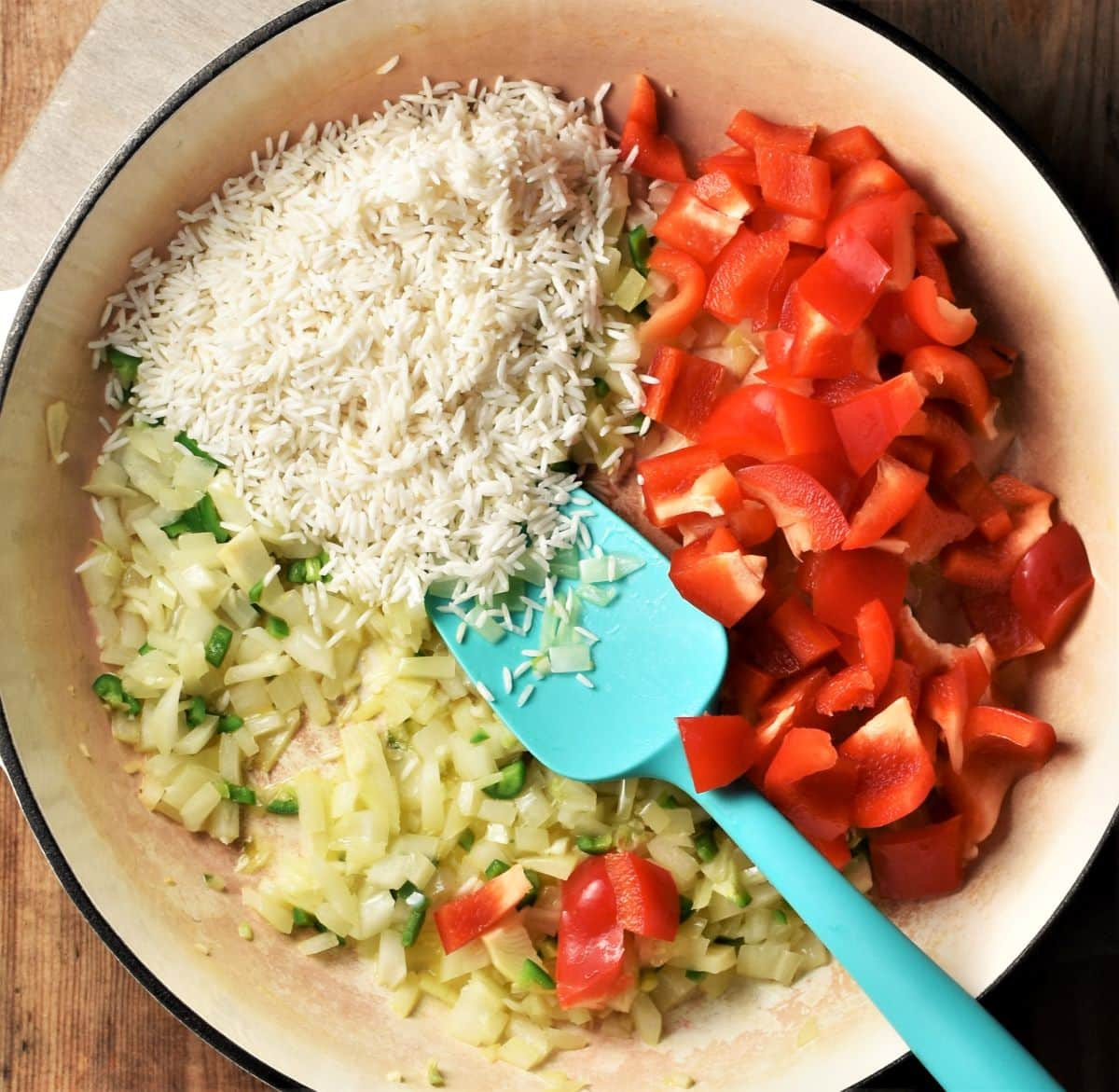 Rice, onion and red pepper in large shallow pan with blue spoon.