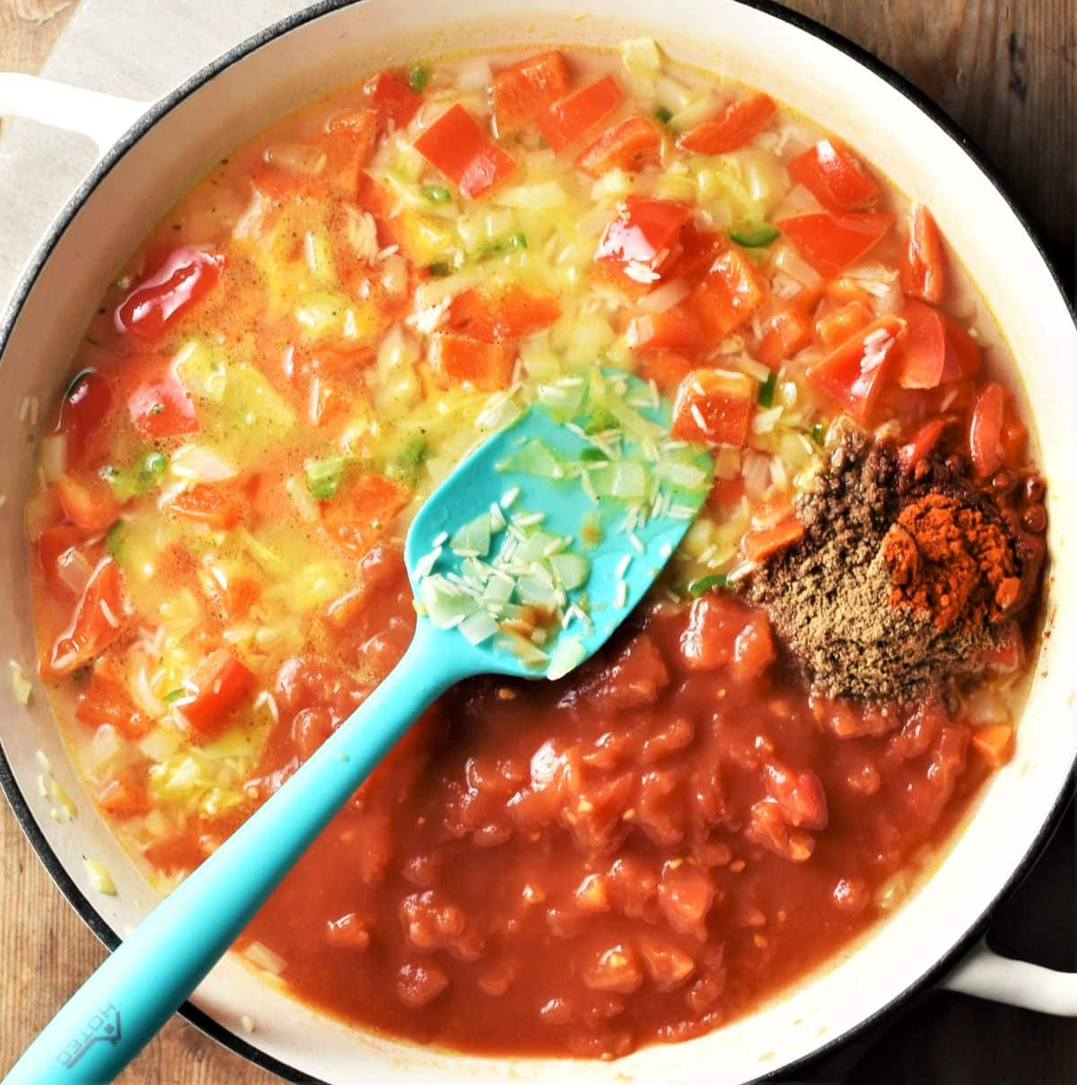 Tomatoes, rice and vegetable mixture in large pan with blue spoon.