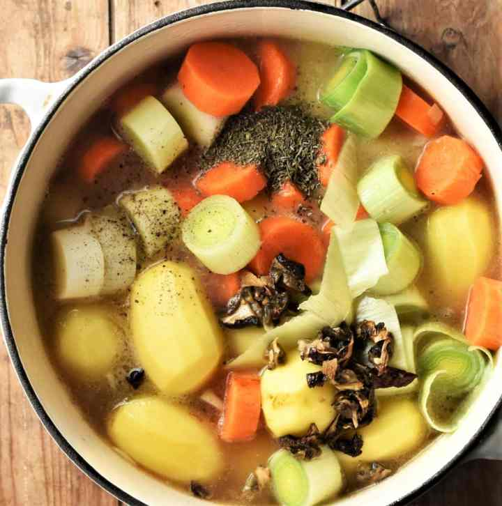 Potatoes and vegetables with stock in pot.