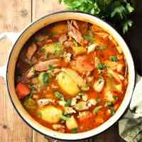Chicken potato stew with vegetables and herbs in pot.