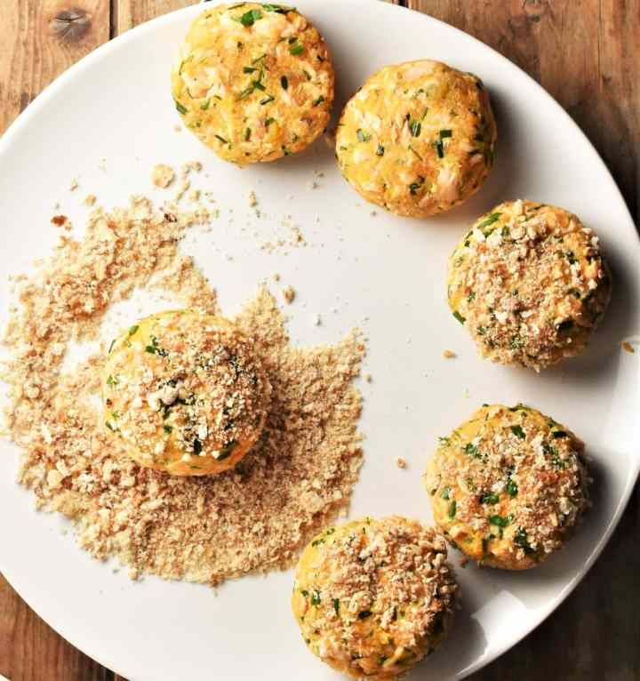 Coating salmon fish cakes in breadcrumbs on large plate.