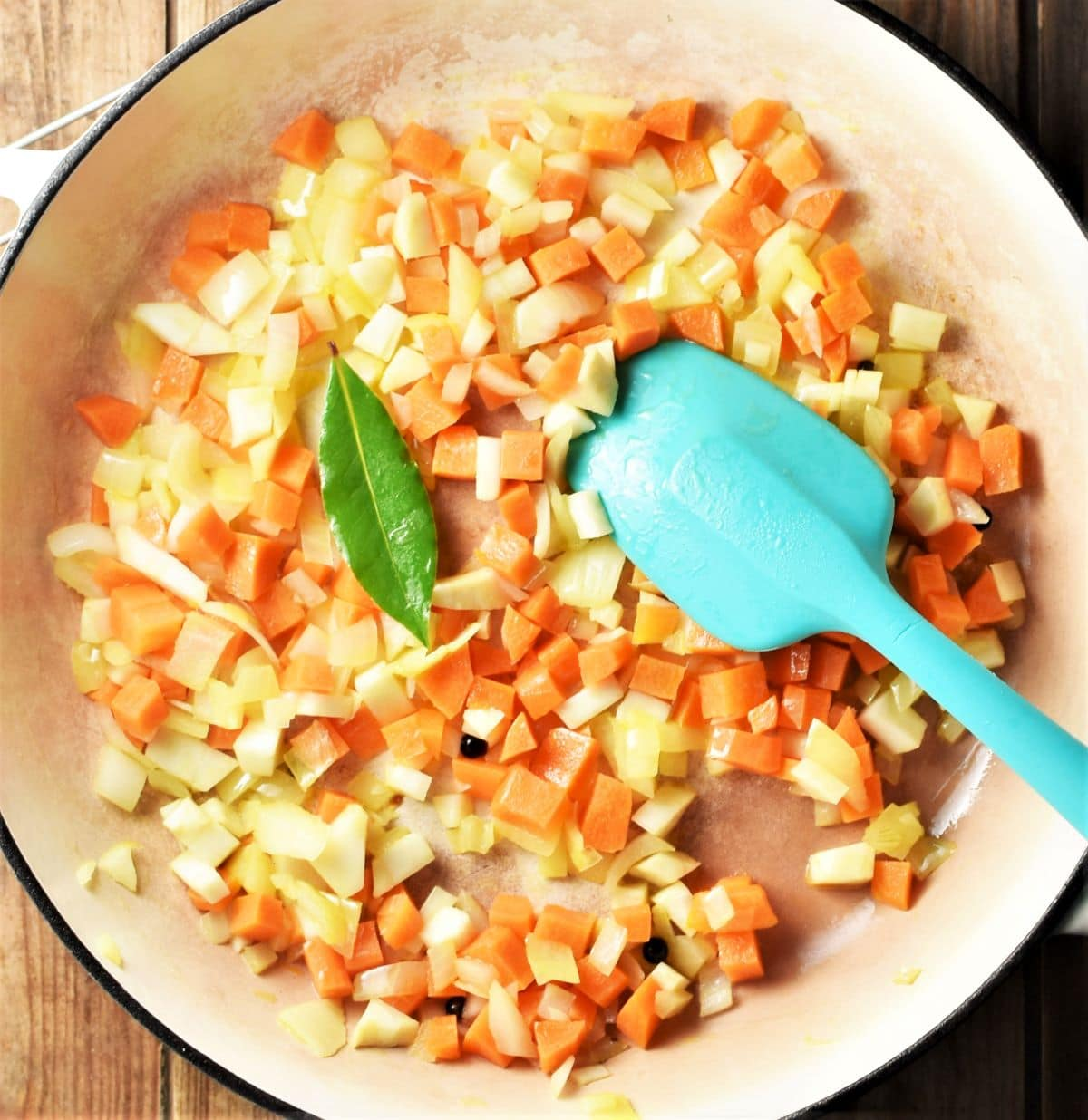 Diced vegetables in large pan with blue spoon.