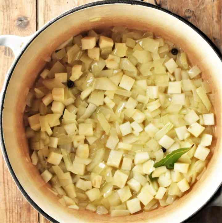 Diced onion and celery root with bay leaf cooking in pot.