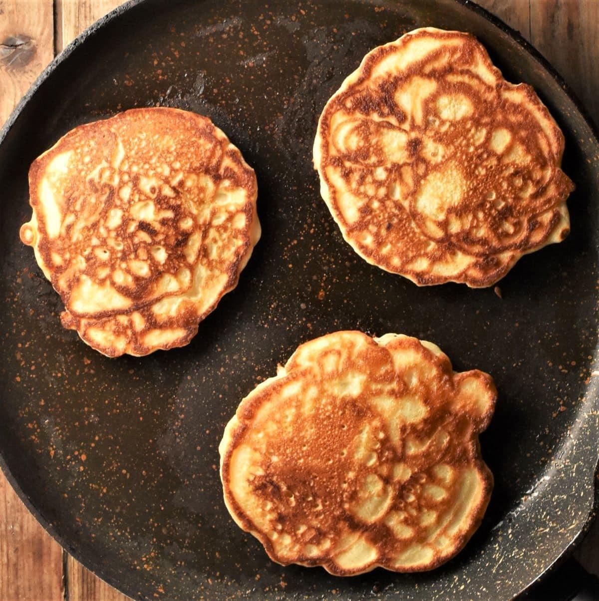 3 pancakes on top of large frying pan.