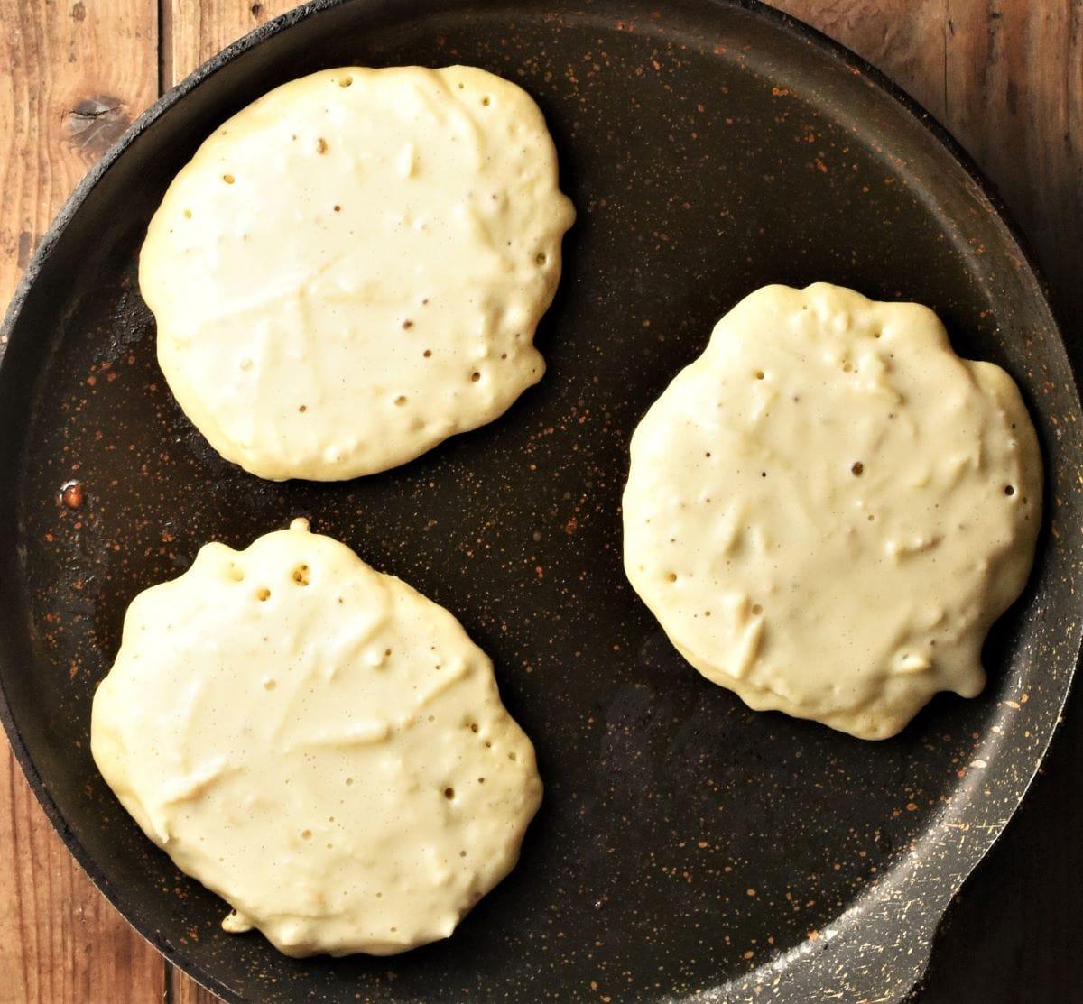 Frying 3 apple pancakes in large pan.
