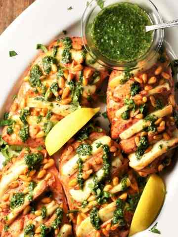 Baked hasselback chicken breasts with halloumi, herb sauce and lemon wedges in white dish.