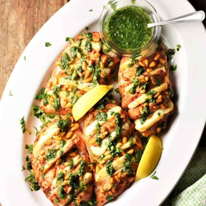 Baked hasselback chicken with halloumi, lemon wedges and herb sauce in oval white dish.