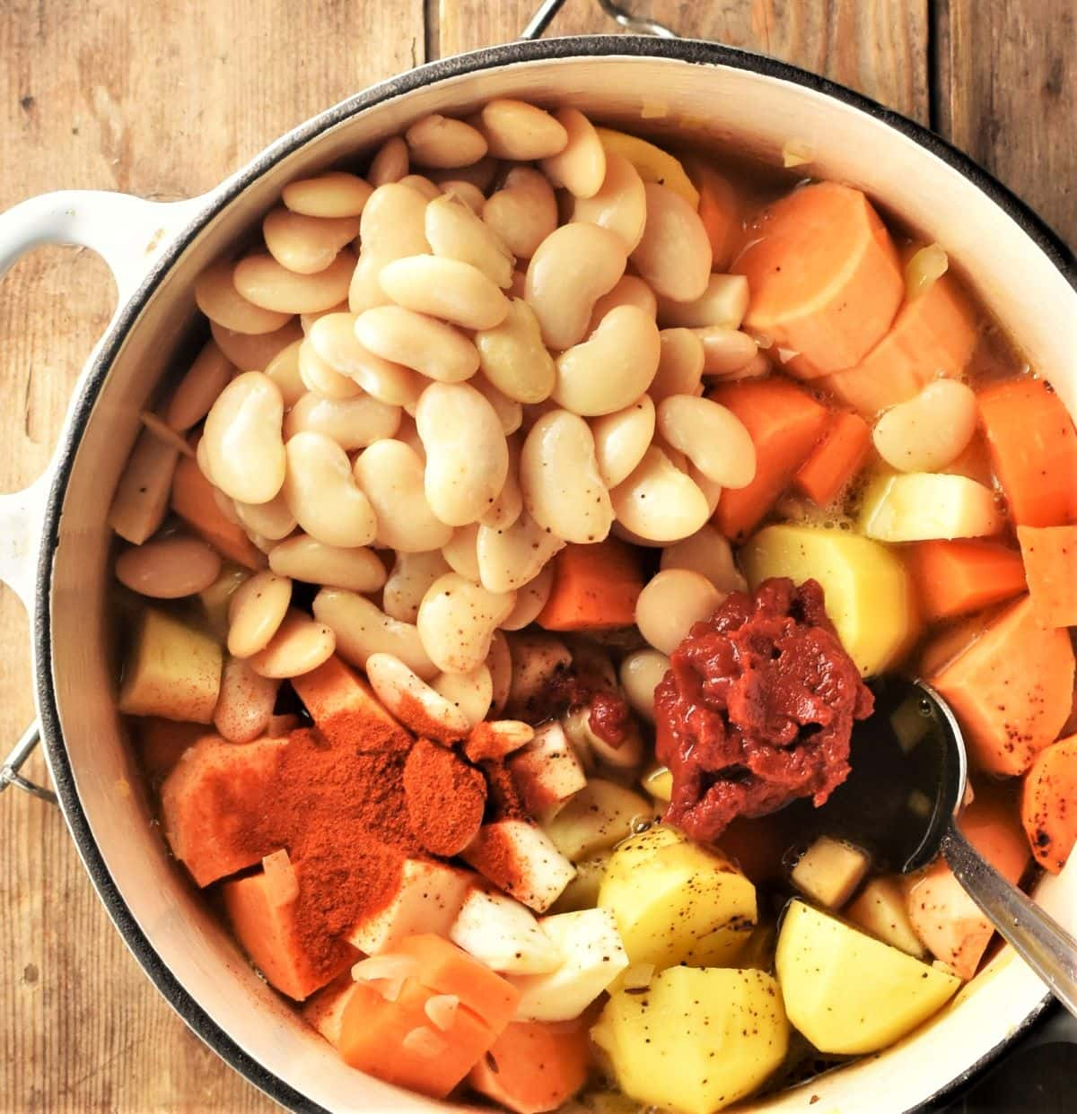 Assembling root vegetables, beans and spices in large pot with spoon.