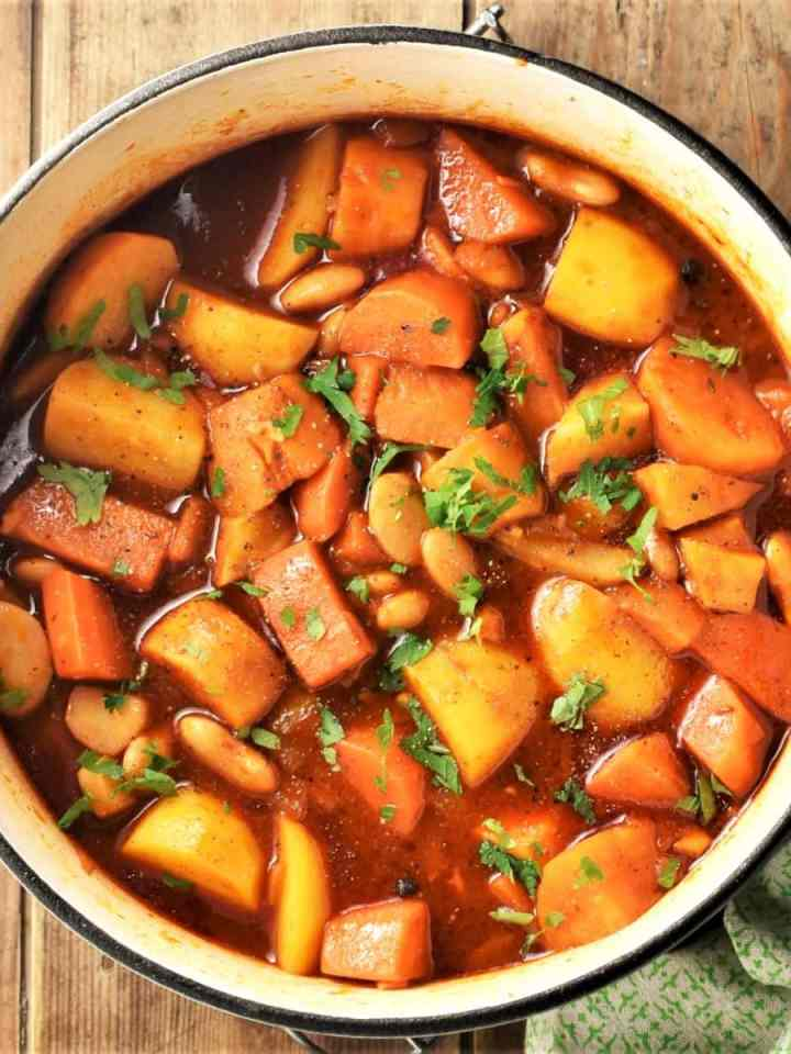 Root vegetable stew with chopped parsley in large pot.