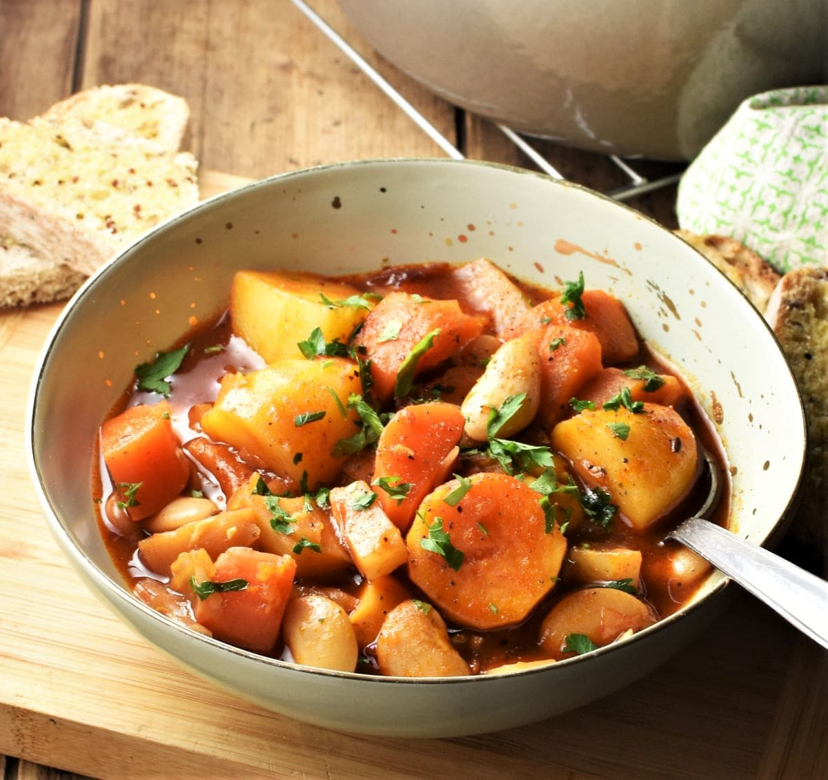 Side view of root vegetable stew in green bowl with spoon and bread in background.