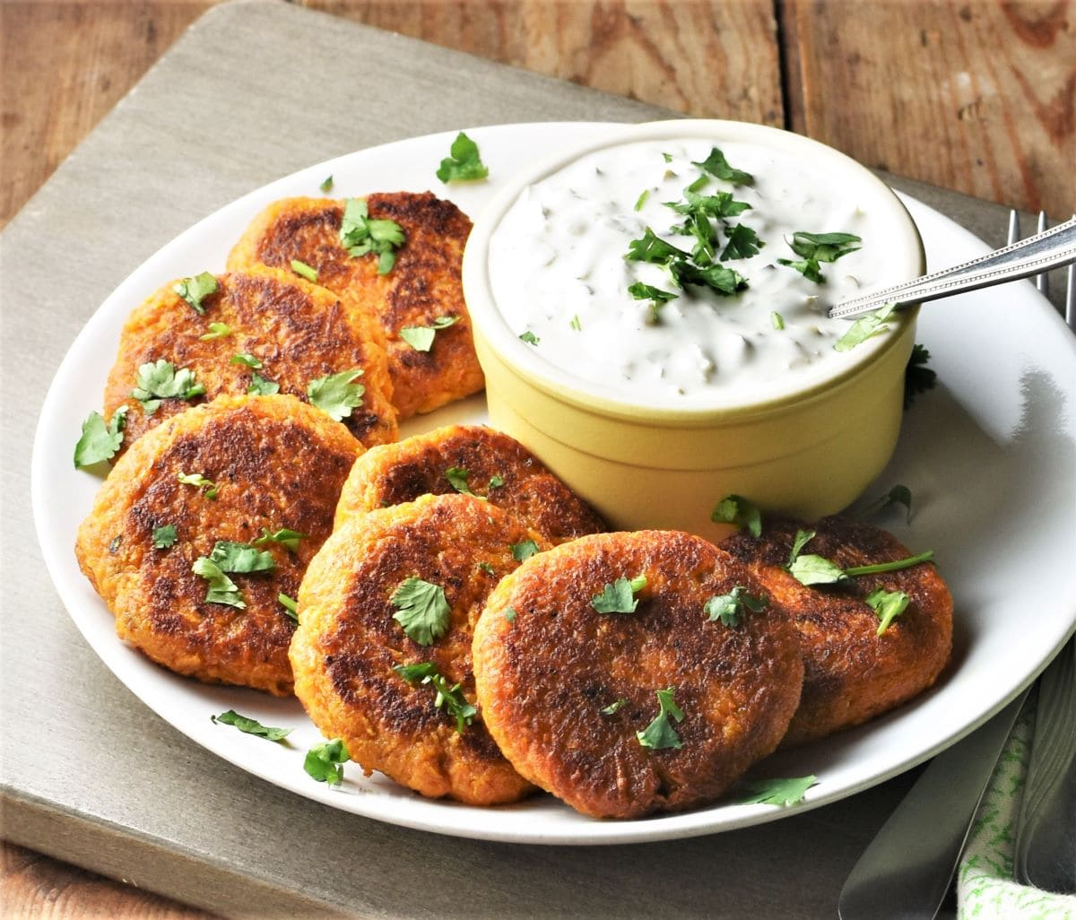 Side view of sweet potato cakes on top of plate with yogurt dip in the middle.