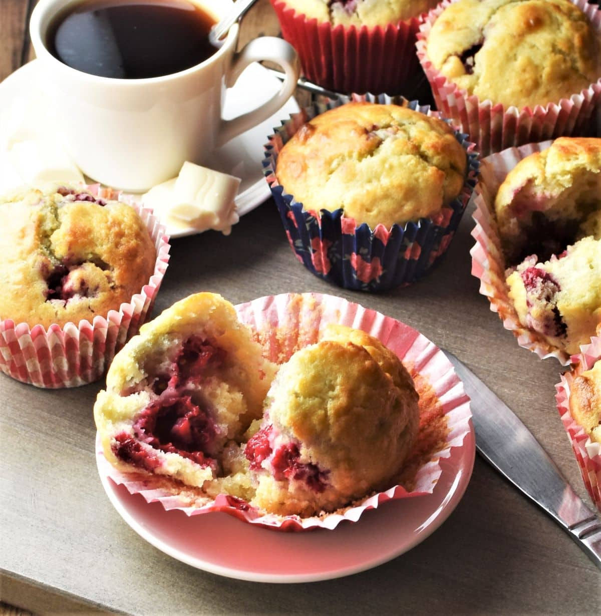 Side view of raspberry muffins in paper cases and coffee in background.