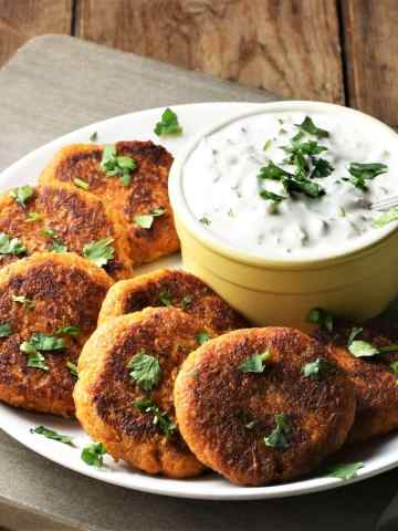 Side view of sweet potato fritters on top of plate with yogurt dip in yellow dish.