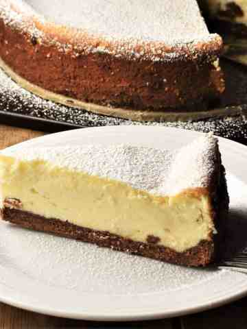 Side view of Polish cheesecake slice on top of whit plate with cheesecake in background.