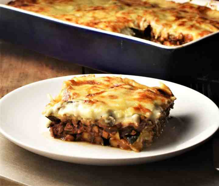 Side view of lentil mushroom moussaka slice on top of white plate with moussaka in background.