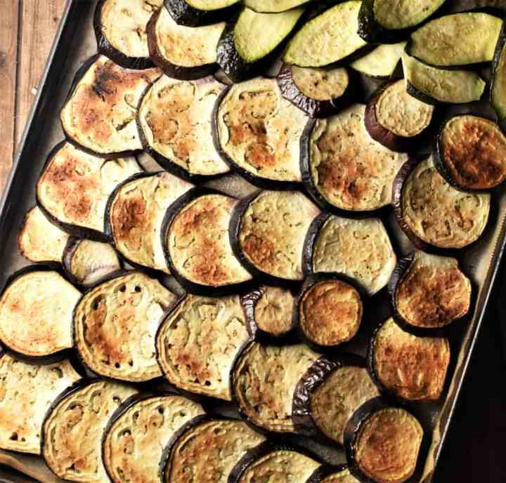 Lightly browned slices of eggplant and zucchini on top of baking sheet.