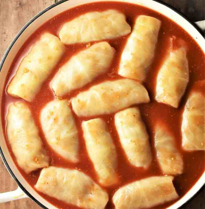 Cabbage rolls with tomato sauce in large pan.