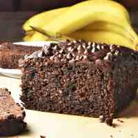 Side view of chocolate banana cake with bananas in background.