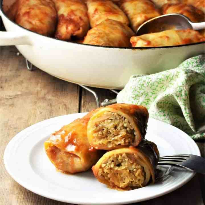 Side view of sauerkraut cabbage rolls on top of plate and in casserole dish in background.