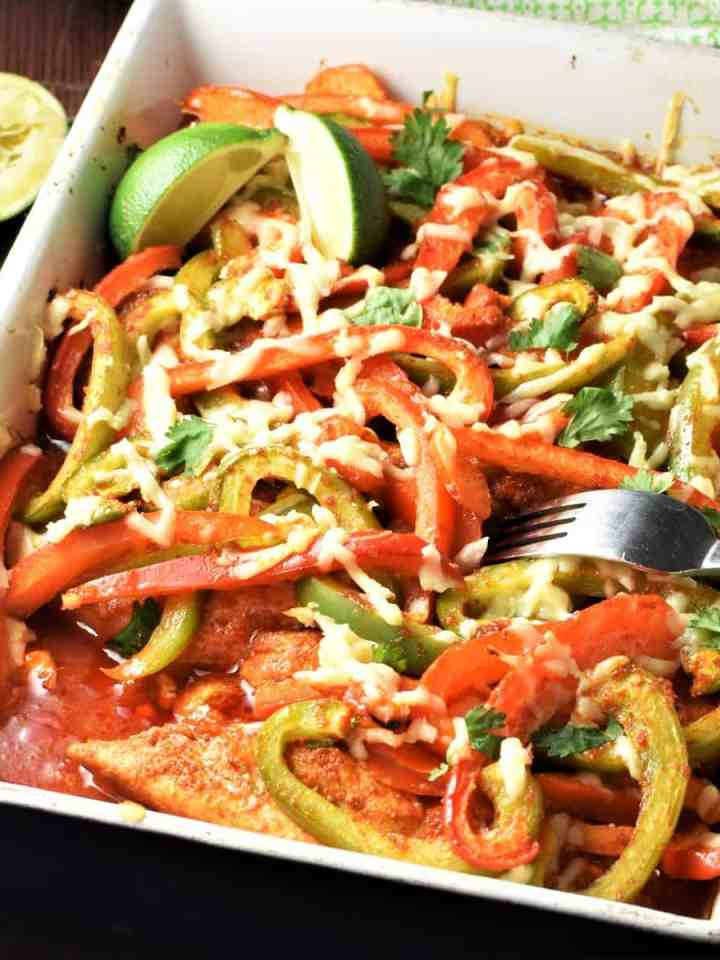 Side view of chicken fajitas casserole with fork and lime in background.